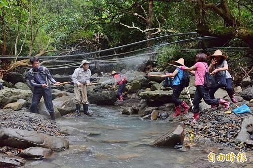 拿起竹筒水槍,像打針筒般放入溪流中抽滿水,再用力一壓就能射出水砲打水戰。(記者許麗娟攝)