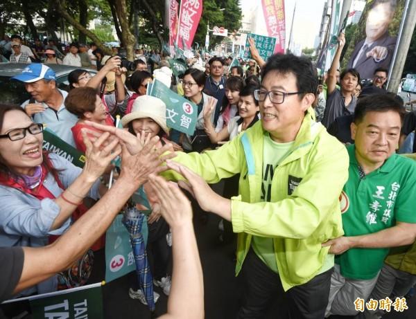 民進黨台北市長候選人姚文智下午於市府路舉辦「手護國家首都」造勢活動,一一與支持者擊掌。(記者方賓照攝)