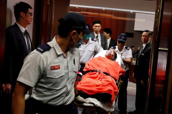 發生推擠衝突後,多名保全稱身體不適後,戴著氧氣罩、躺在擔架上被抬離現場。(路透)