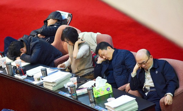 Legislators from the ruling and opposition camps nap at the legislature in Taipei early yesterday morning during an overnight review of amendments to the Labor Standards Act. Photo: Liu Hsin-de, Taipei Times