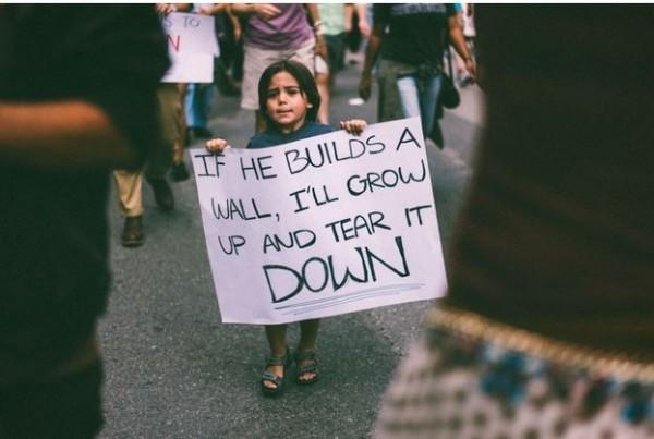 小男孩手中緊握著一張大大的標語板,上面寫著「如果他蓋了牆,我會長大並把它拆掉」。(擷取自huffingtonpost)