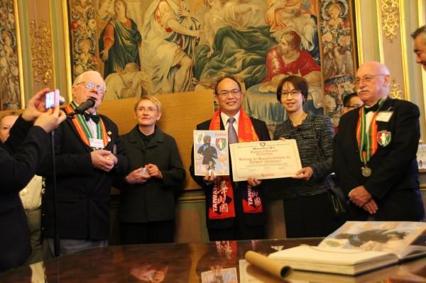 駐歐盟兼駐比利時代表曾厚仁(右3)今天出席台灣捐贈客家服飾給尿尿小童儀式並獲得證書及貼紙,左2為布魯塞爾市文化局長范登柏爾克。(中央社)