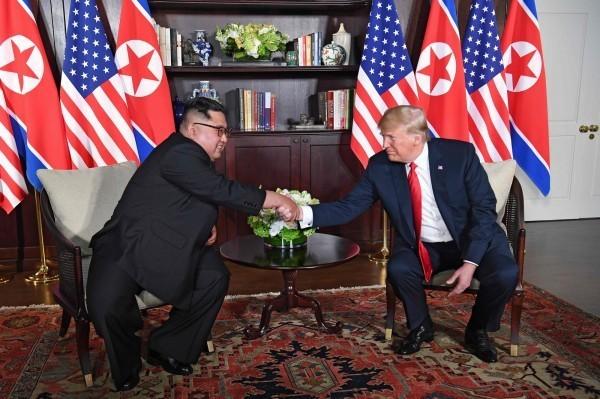 川普與金正恩開始進行一對一會晤後,一改握手時的笑容,兩人坐下後表情略顯嚴肅,不過在翻譯的協助下開始進行對談。(法新社)