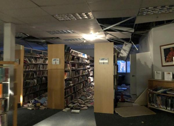 安克拉治一所學校的圖書館天花板被震落,架上書籍也一片狼籍。(法新社)