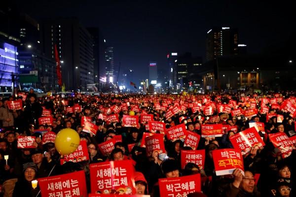 超過7成南韓人想移民,最主要原因是逃避國內過於激烈的競爭環境,其次是對腐敗政府的失望感。圖為跨年夜南韓民眾集會抗議,要求總統朴槿惠下台。(路透)