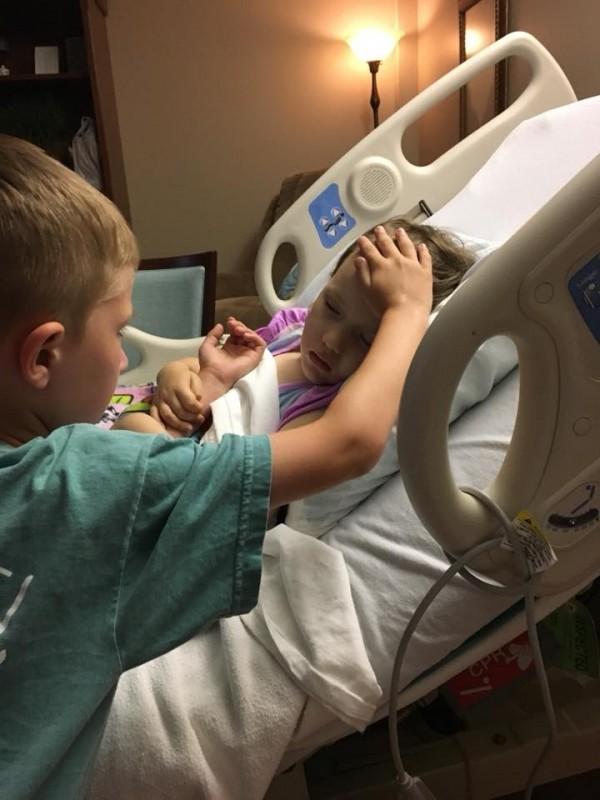 美國一名悲傷的父親在臉書上分享一張照片,照片中一名6歲的小哥哥站在病床前,一手撫摸著閉眼躺在床上,神情虛弱的妹妹,另一手則被妹妹環抱住。(圖擷取自臉書)