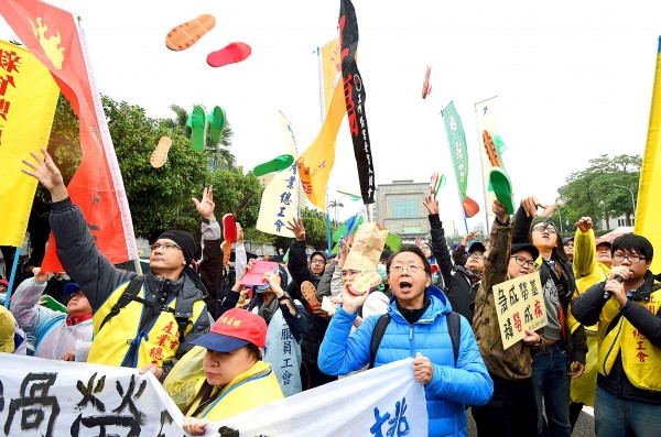 Taoyuan Confederation of Trade Unions members fling sandals toward the Presidential Office Building in Taipei yesterday to protest draft amendments to the Labor Standards Act. Photo: Peter Lo, Taipei Times