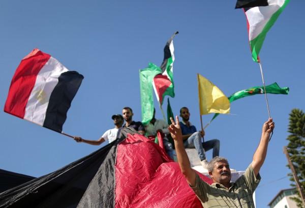 巴勒斯坦民眾揮舞著埃及、巴勒斯坦、法塔組織和哈瑪斯的旗幟。(法新社)