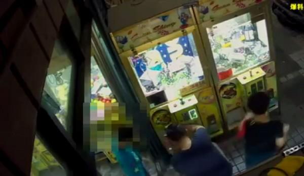 高雄一名爸爸讓孩子鑽進機台內撥下商品後,自己再蹲下從洞口取出。(圖擷自爆料公社)