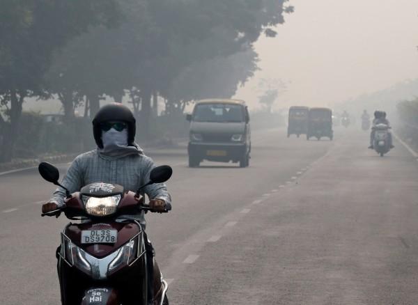 防止吸入髒空氣,機車騎士全身包得密不透風。(路透)