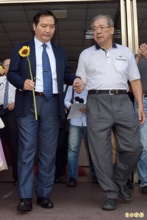 蘇炳坤(圖右)和律師羅秉成步出法,接受媒體訪問,並有司改團體獻上向日葵祝賀。(記者黃耀徵攝)
