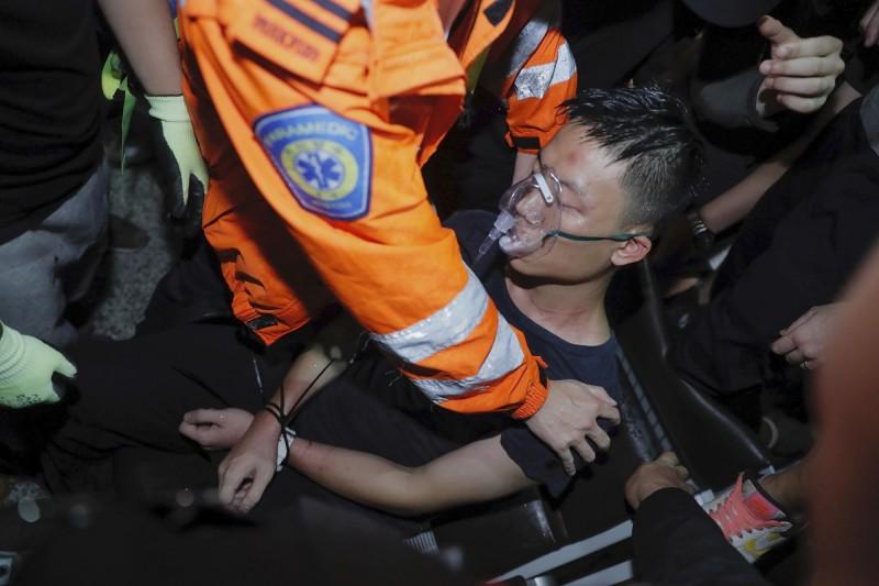 疑為中國公安的男子雙手被束帶捆綁,稍晚被醫護人員抬上擔架、送上救護車。(美聯社)