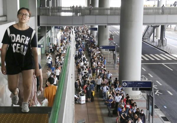 受困於關西機場旅客脫困,露出疲態。(美聯社)