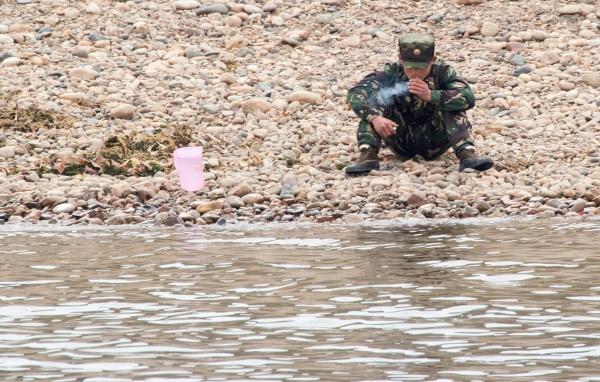 位於中韓邊境的北韓士兵,若無其事地抽著菸。(法新社) <b>☆自由電子報關心您,吸菸有害健康☆</b>