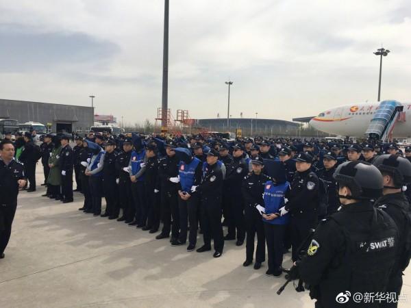 78名台灣詐騙犯戴著頭套下機,每位詐騙犯左右都由中國公安架住,頂著太陽在停機棚上排成一列。(圖擷自臉書「China Xinhua News」)