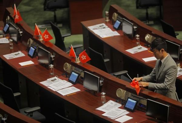 建制派議員集體離席後,「熱血公民」的鄭松泰將議會桌上的五星旗與港旗倒插。(美聯社)
