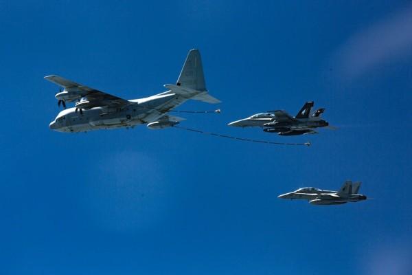 駐日美軍一架KC-130空中加油機與一架F/A-18大黃蜂式戰鬥機今天凌晨在日本四國島外海相撞墜海。圖為2016年10月美軍2架F/A-18大黃蜂式戰鬥機和KC-130空中加油機進行加油演習。(美聯社)
