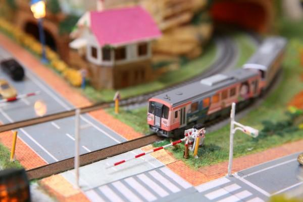 列車經過、平交道柵欄擋下人、車,背景音傳來「叮噹~叮噹~」聲,眼前場景就是生活中再熟悉不過的平交道號誌系統模型場景。(記者潘自強攝)