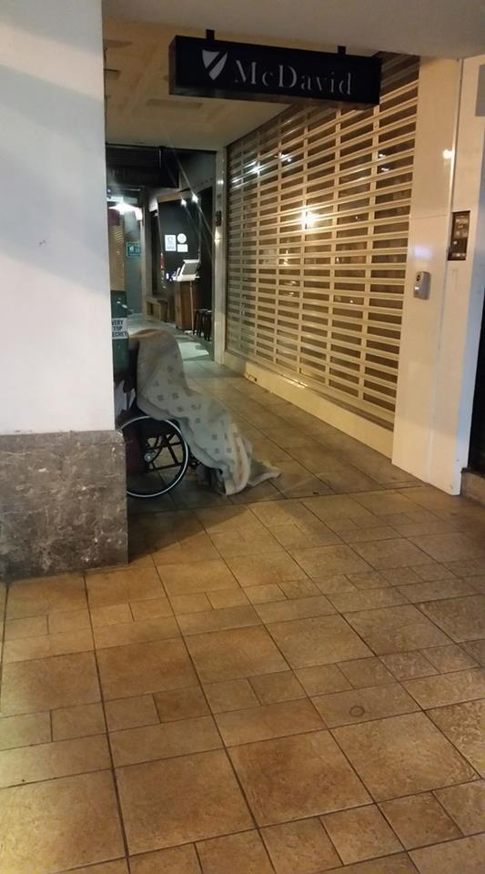 台北昨日晚間,街頭驚現一名街友全身罩上白毯睡在輪椅上,不知情的民眾以為發生事故,立刻報警處理。(圖擷自爆料公社)