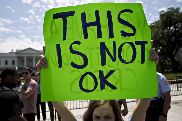 川普與俄外長會面,抗議者在白宮外高舉「不可行」的標語。(彭博)