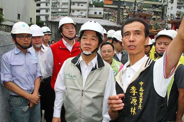 Premier William Lai, center, yesterday says during a visit to Keelung that he hopes the 3 percent pay raise for government employees next year will stimulate the economy. Photo: Lin Hsin-han, Taipei Times