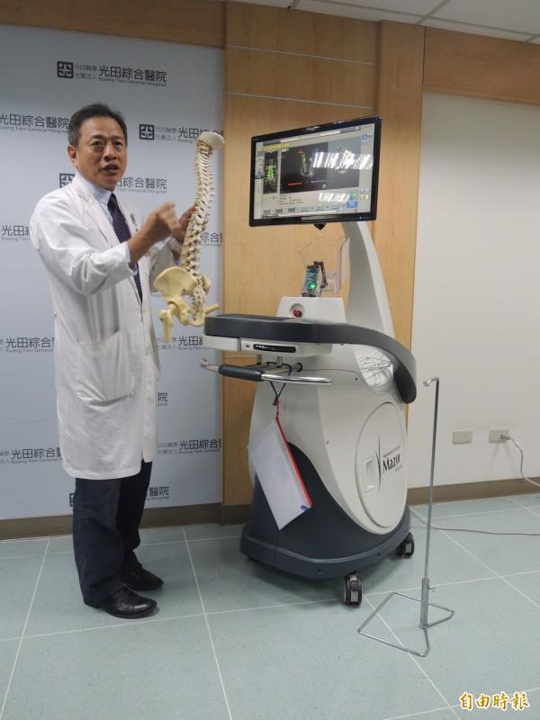 光田醫院院長陳子勇說明雷納生機械手臂效能。(記者張軒哲攝)
