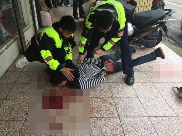 江男被逮補壓制在地,地面都是他砍殺古男遺留的血跡。(記者彭健禮翻攝)