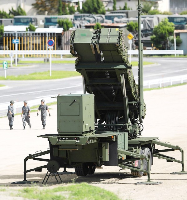 Military yesterday walk past a missile interceptor at a base in Kaita, Japan. Photo: AFP
