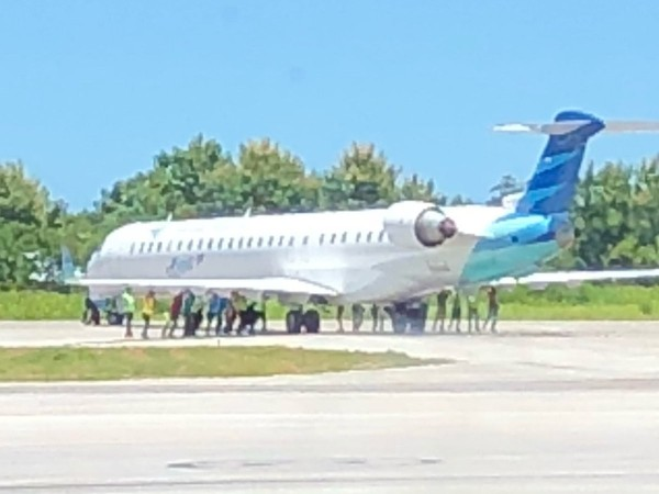 印尼一機場出動20人以徒手方式,把飛機向後推到應到的停機坪。(圖取自推特)