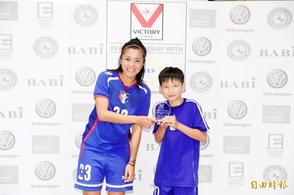 Royal Dragons forward Danny Carroll, right, receives a Most Valuable Player trophy from a Taiwan Mulan soccer representative at the Football Festival at the Taipei European School last month. Photo courtesy of Michael Chandler of MFA