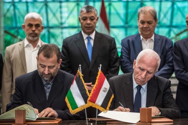 在負責監督談判的埃及情報部門見證下,法塔組織談判代表團長阿邁德(Azzam al-Ahmed)和哈瑪斯副領導人阿盧里(Salah al-Aruri)簽署協議。(法新社)