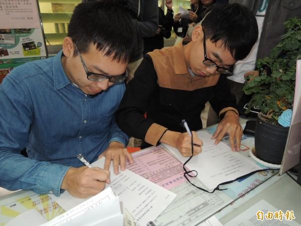 台南市與新北市昨天開放同性伴侶註記,南市的楊智達(左)、洪國峰(右)前往東區戶政事務所填寫註記申請書。(資料照,記者王俊忠攝)