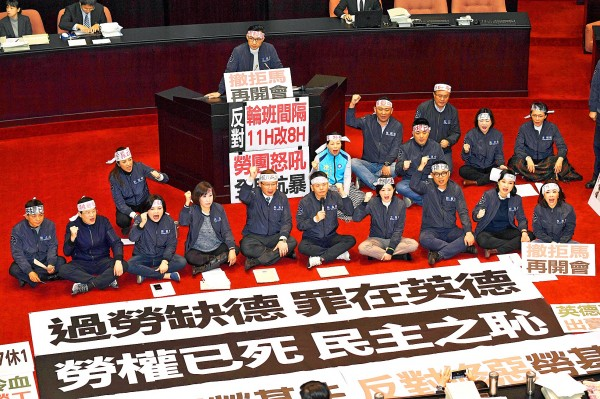Chinese Nationalist Party (KMT) legislators spread banners and chant slogans on the floor of the Legislative Yuan in Taipei yesterday during deliberations on the government's proposed amendment to Article 24 of the Labor Standards Act. Photo: CNA