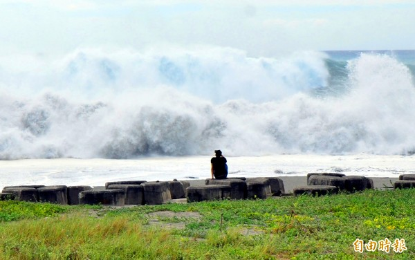 A person sits on breakwater blocks in Taitung County yesterday and watches the high waves caused by Typhoon Mangkhut as they hit the coast.