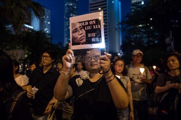 參與遊行的民眾手舉「劉霞 挺住!」的標牌,希望劉霞能盡快獲得自由。(法新社)