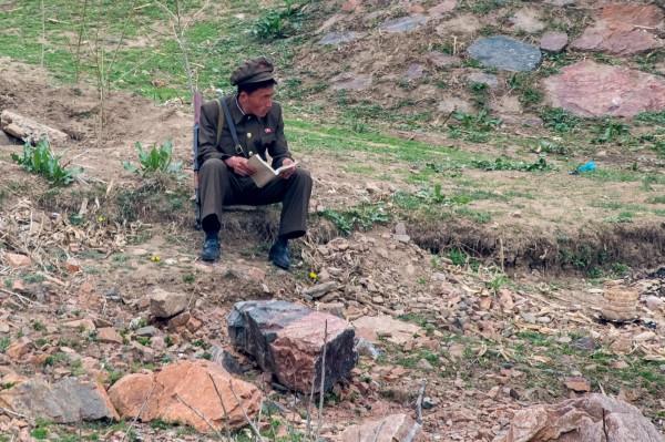 北韓士兵坐在江邊看書。(法新社)