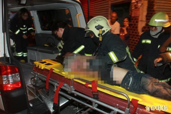 花蓮縣吉安鄉南海四街一處民宅今晚傳出火警,事後消防人員從二樓抬下一名性命垂夗的陌生人,嚇壞住在一樓的屋主。(記者王錦義攝)