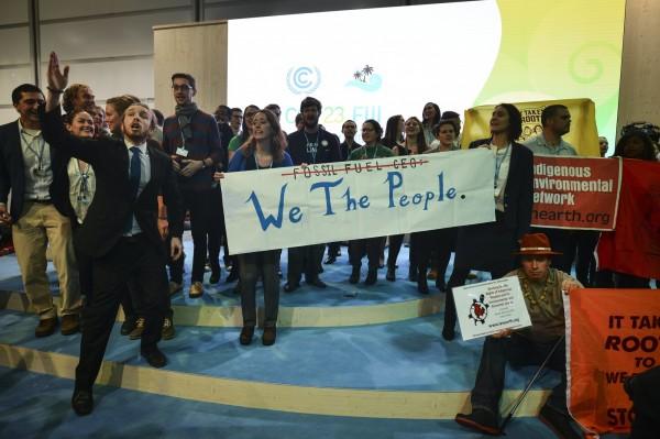 美國在聯合國氣候變遷會談時發表支持煤炭使用的報告,遭到數十名抗議人士衝上台,以「天佑美利堅」曲調,唱著「所以你自稱是美國人,但我們直直看穿你的貪婪」的歌詞,阻擾報告。(歐新社)