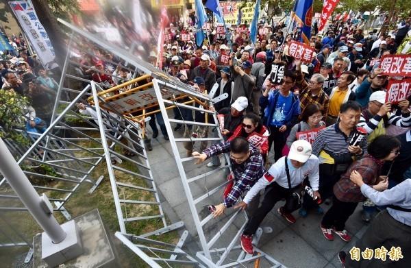 活動當天,成員推倒護欄企圖衝進座談會會場。(記者羅沛德攝)