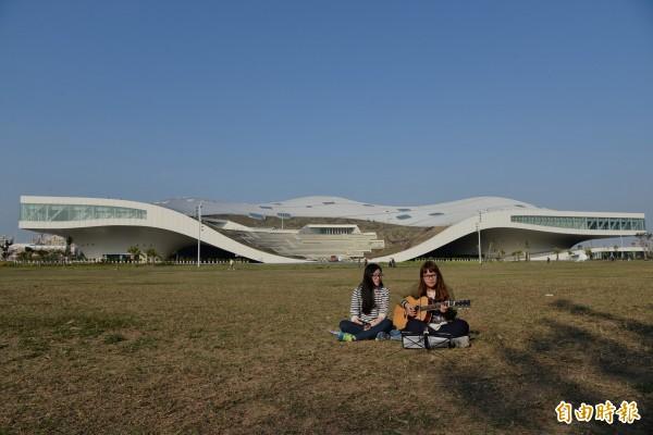 由衛武營都會公園的大草坪,可見衛武營國家藝術文化中心白色流線的新建築樣貌。(記者許麗娟攝)