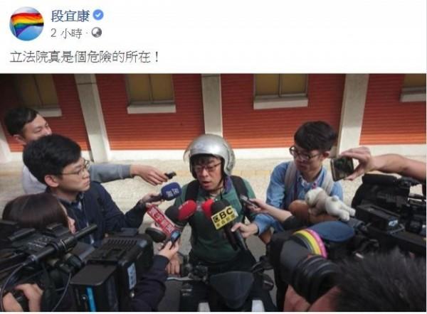 段宜康將戴安全帽遭媒體包圍的照片貼上臉書,幽默表示,「立法院真是個危險的所在!」(圖擷自臉書)