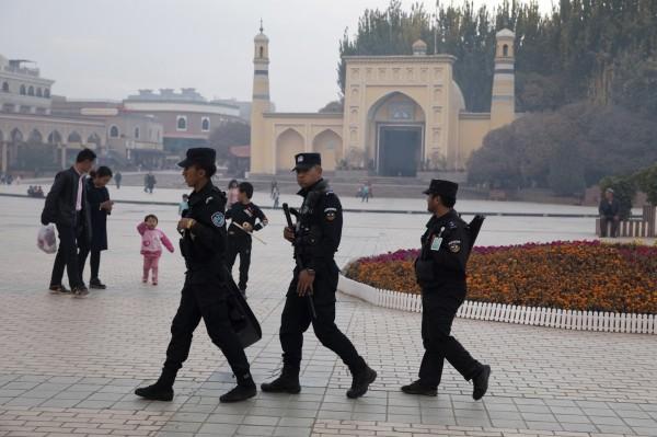 中國新出爐的法條明文容許政府設立「教育轉化機構」,等同將「再教育營」這類被國際社會批評有違人權的機構,正式寫入法律。圖為安全人員在新疆一座清真寺附近巡邏。(美聯社)