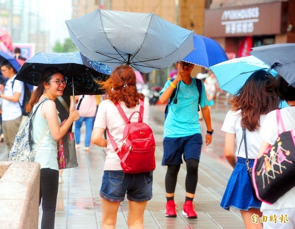 A woman laughs as her friend's umbrella is blown inside-out in Taipei yesterday afternoon as Typhoon Maria began to affect northern Taiwan.