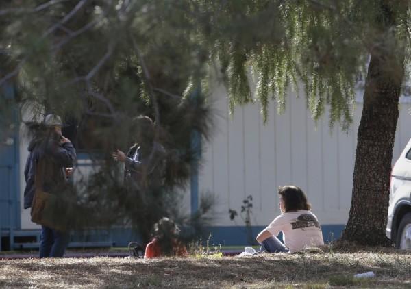 美國加州發生隨機槍擊案,劫後餘生的婦人和小孩。(美聯)