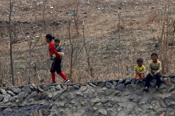 北韓孩童在一旁好奇地看著攝影鏡頭。(路透)