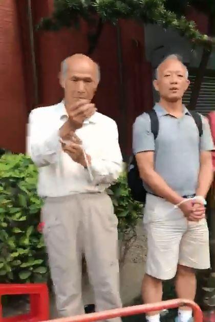 反年改成員看到鏡頭在拍,急忙把手套入束帶。(圖翻攝自臉書)