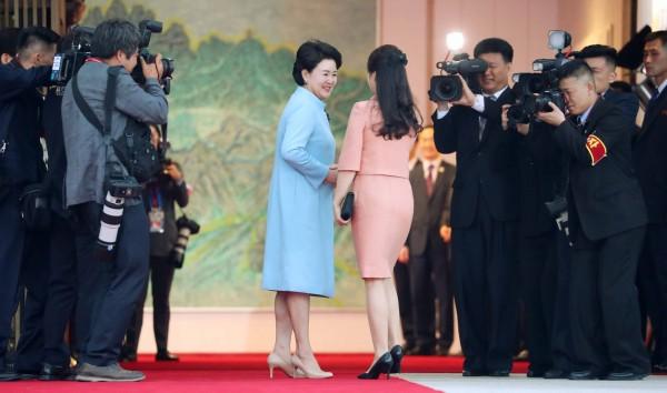 聯合晚宴開始前,先到場的金正淑特地到門口迎接李雪主,雙方握手後一起步入會場。(法新社)