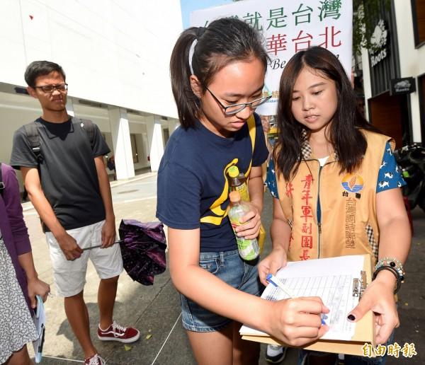 台灣團結聯盟13日在西門站舉辦「2020東京奧運台灣正名,街頭連署暨記者會」,青年部主任許亞齊(右)邀民眾連署,希望能夠一舉衝破連署門檻,提供發起連署的「台灣正名推進協議會」提及給東京都議會,讓「台灣隊」取代「中華台北」,在東京奧運的賽場上與其他國家一天競爭桂冠。(記者簡榮豐攝)