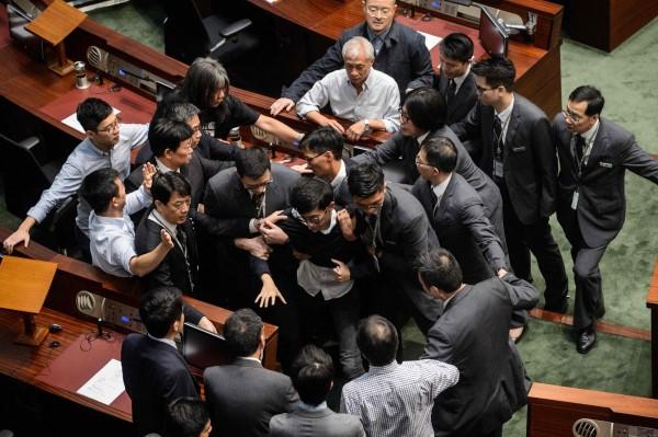 香港本土派議員梁頌恆、游蕙禎因先前在宣誓儀式時稱中國為「支那」,遭判定宣誓無效且禁止宣誓,今梁、游2人嘗試進入立法會會議室並與保全人員發生衝突。(法新社)