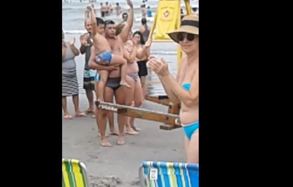 巴西一名男童在海灘走失,找不到媽媽,有個壯漢遊客把他抱起,其他遊客見狀紛紛拍手鼓掌,吸引媽媽注意,順利讓母子重逢。(圖擷取自「ViralHog」YouTube影片)